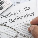 Close up of bankruptcy petition with calculator and writing hand